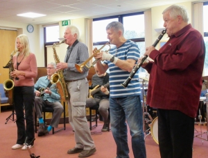 Four people playing brass/woodwind instruments, with a guitarist, bass guitarist and drummer in the background.